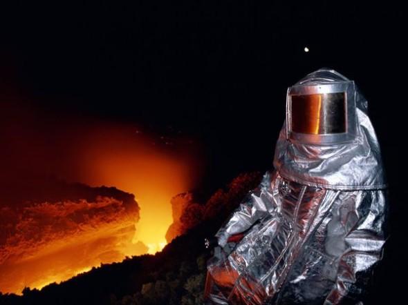 """Protetto da una tuta termica, un vulcanologo raccoglie campioni di lava """"fresca"""" sull'Etna."""
