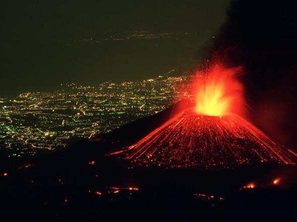 Affacciato sulla città illuminata di Catania, l'Etna spara una fontana di fuoco verso il cielo, mentre rivoli di lava scendono lungo i suoi fianchi. Si tratta di un vulcano relativamente sicuro, con eruzioni rare e compatte, e la lava scende lentamente, dando il tempo alle persone di fuggire
