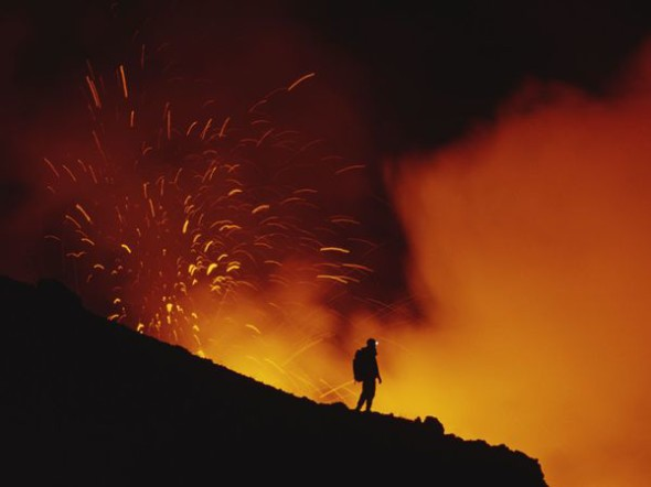 Un ricercatore scientifico osserva un'eruzione dell'Etna, tra i vulcani più attivi al mondo.